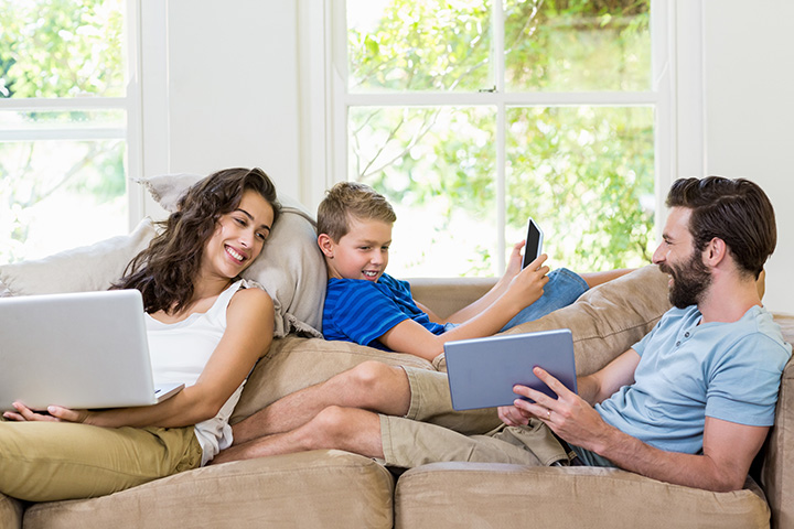 A family on their couch using internet on a laptop, mobile phone, and tablet