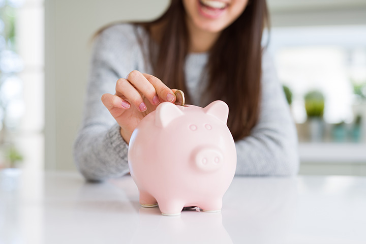 girl-putting-money-in-piggy-bank-smiling