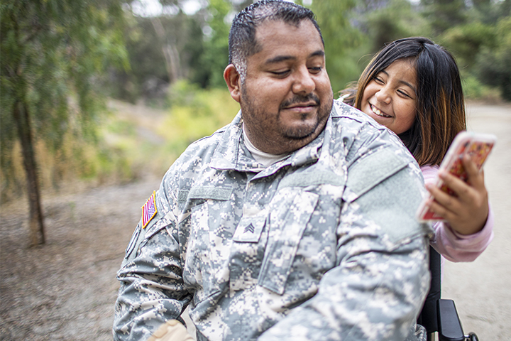 A soldier and his daughter laughing at something on her smartphone