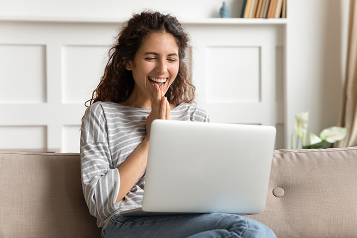 Girl Smiling at Laptop Internet Perks